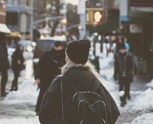 mena de costas com gorro preto andando pelas ruas de Nova York