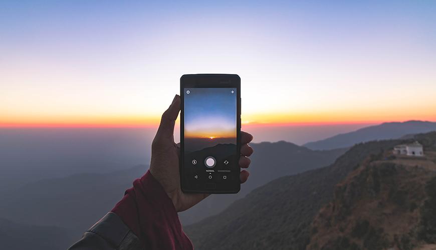 Tela de um celular tirando foto do nascer do sol